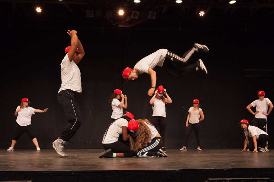 A camper doing a flip during a hip-hop performance