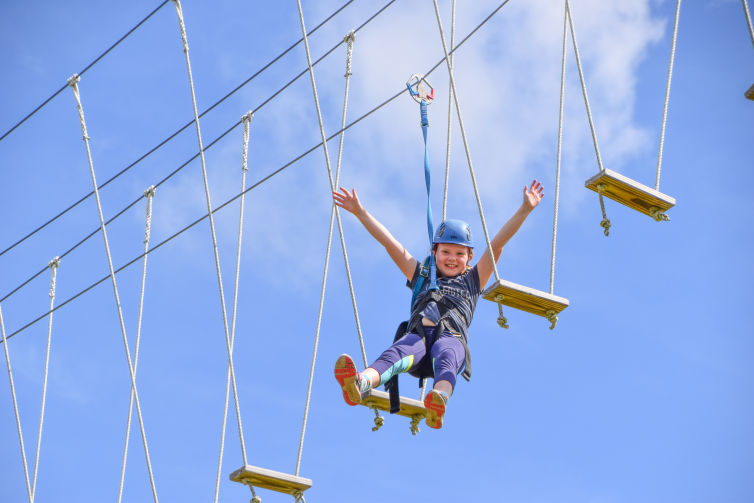 A camper in harness and helmet on our challenge course
